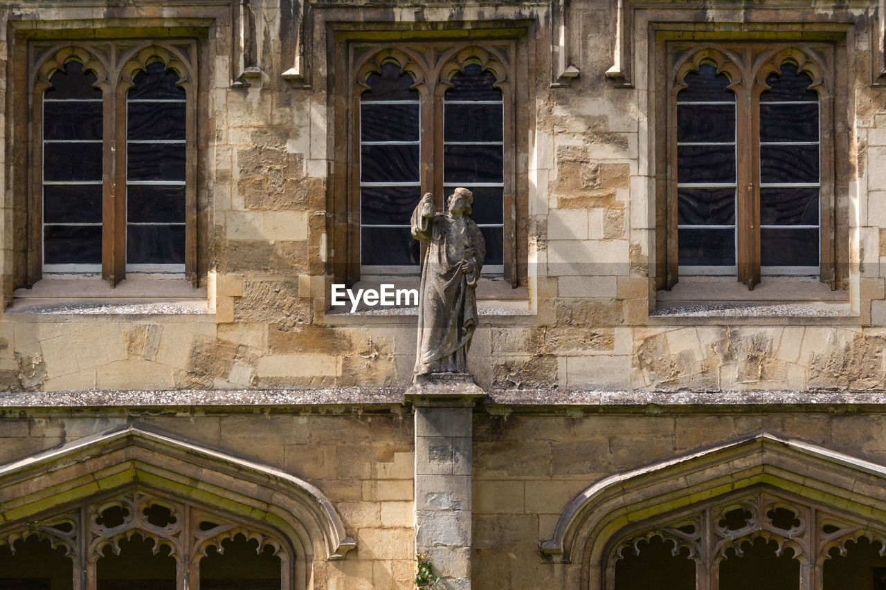 built structure, architecture, building exterior, window, building, statue, sculpture, human representation, day, arch, representation, male likeness, low angle view, the past, no people, history, art and craft, old, creativity, outdoors, architectural column, ornate
