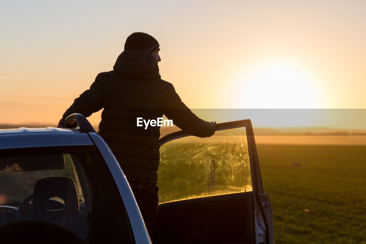 Rear View Of Man Standing On Car Against Sky During Sunset