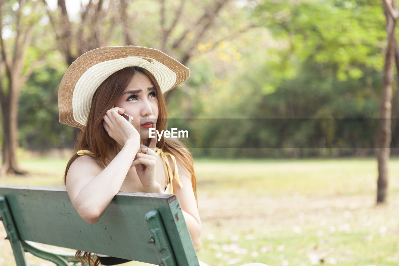 Young woman talking on mobile phone while sitting in park