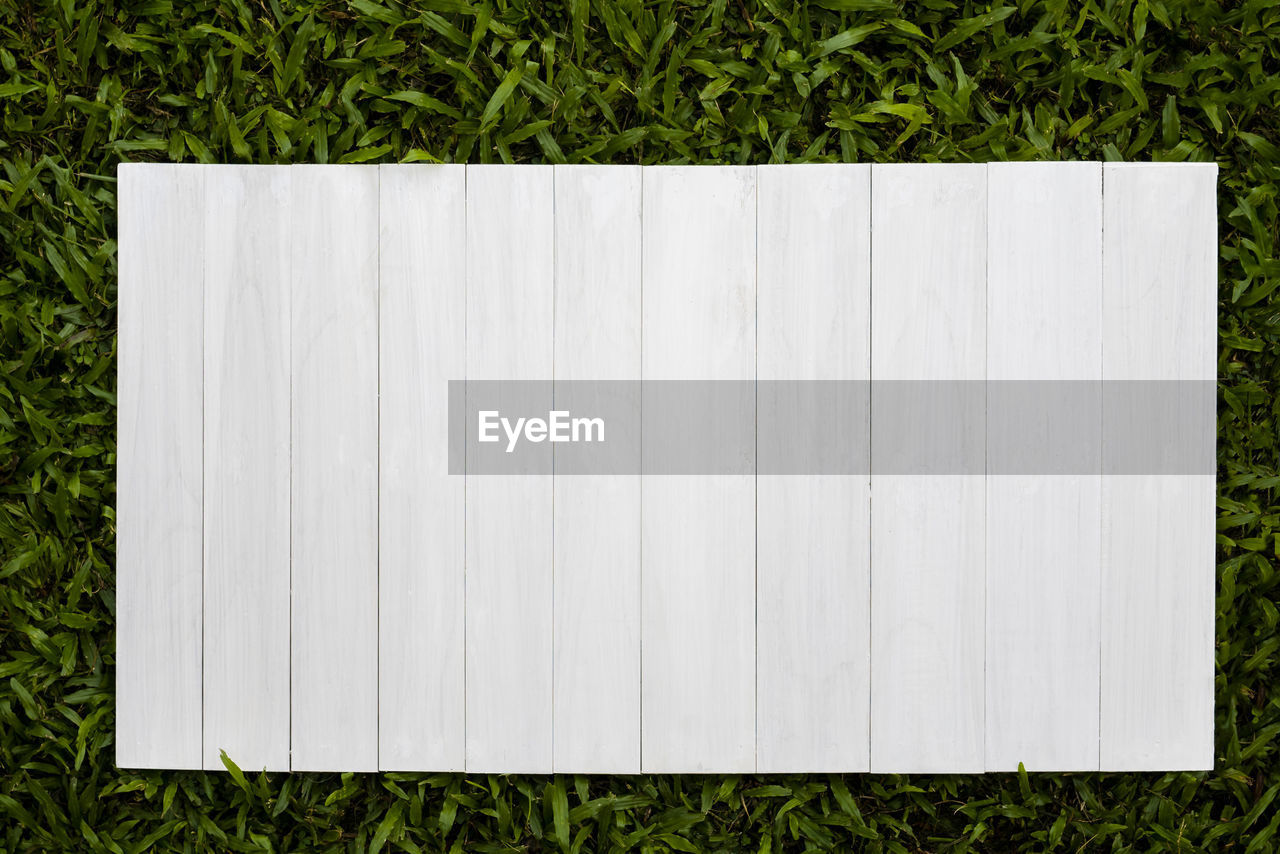 HIGH ANGLE VIEW OF WHITE WOODEN STRUCTURE IN LAWN