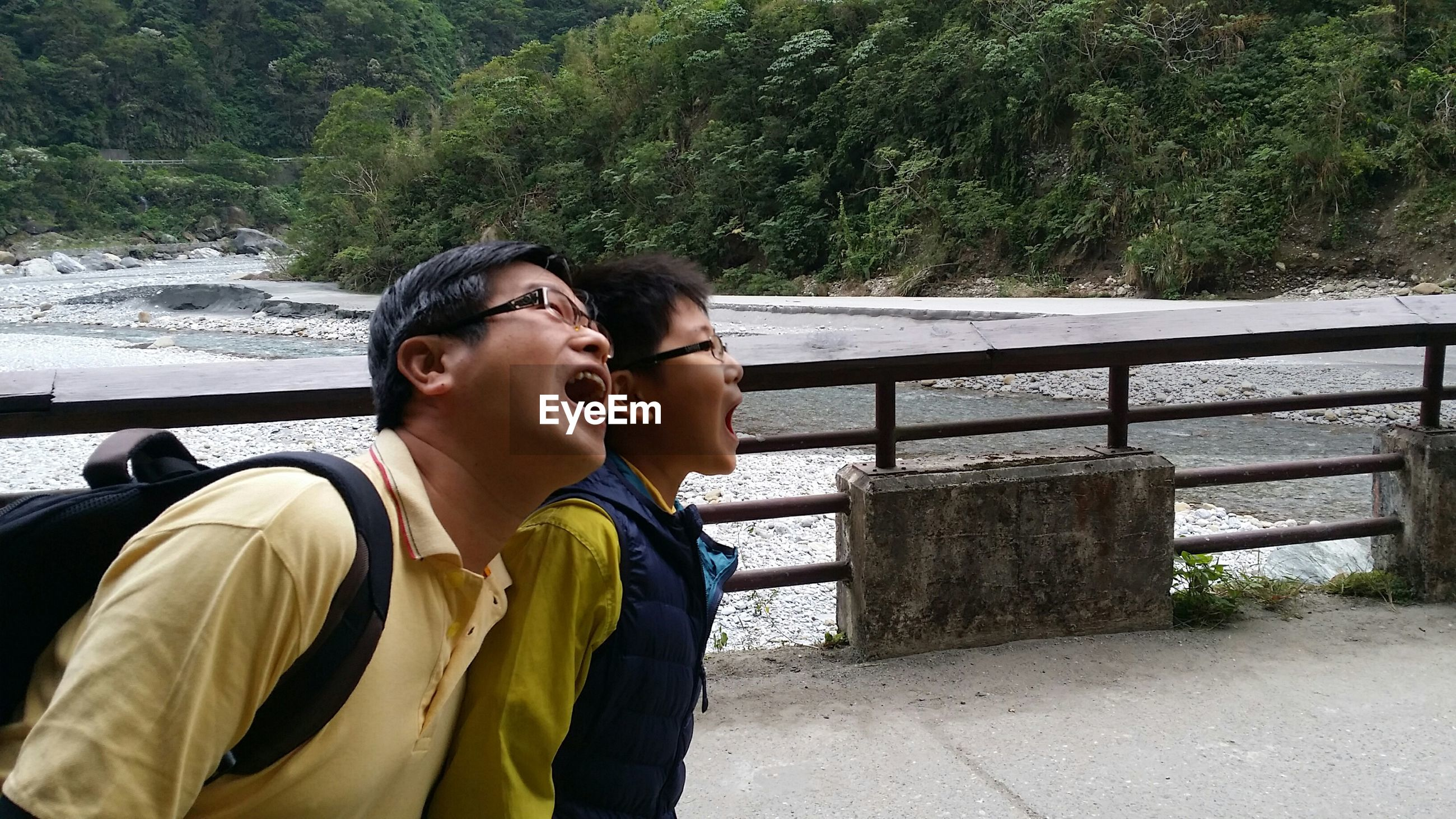 two people, real people, togetherness, love, railing, day, lifestyles, leisure activity, happiness, young women, young adult, water, young men, side view, bonding, outdoors, nature, smiling, couple - relationship, retaining wall, tree, mountain, friendship