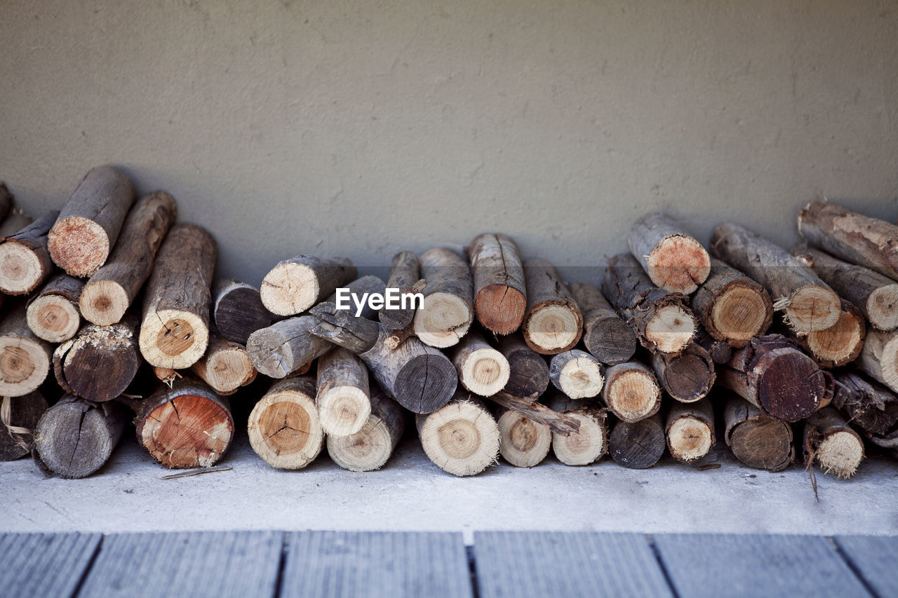 Stacked Logs Against Wall