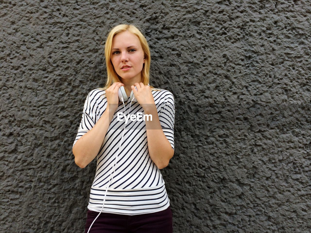 Portrait of young woman with headphones against wall