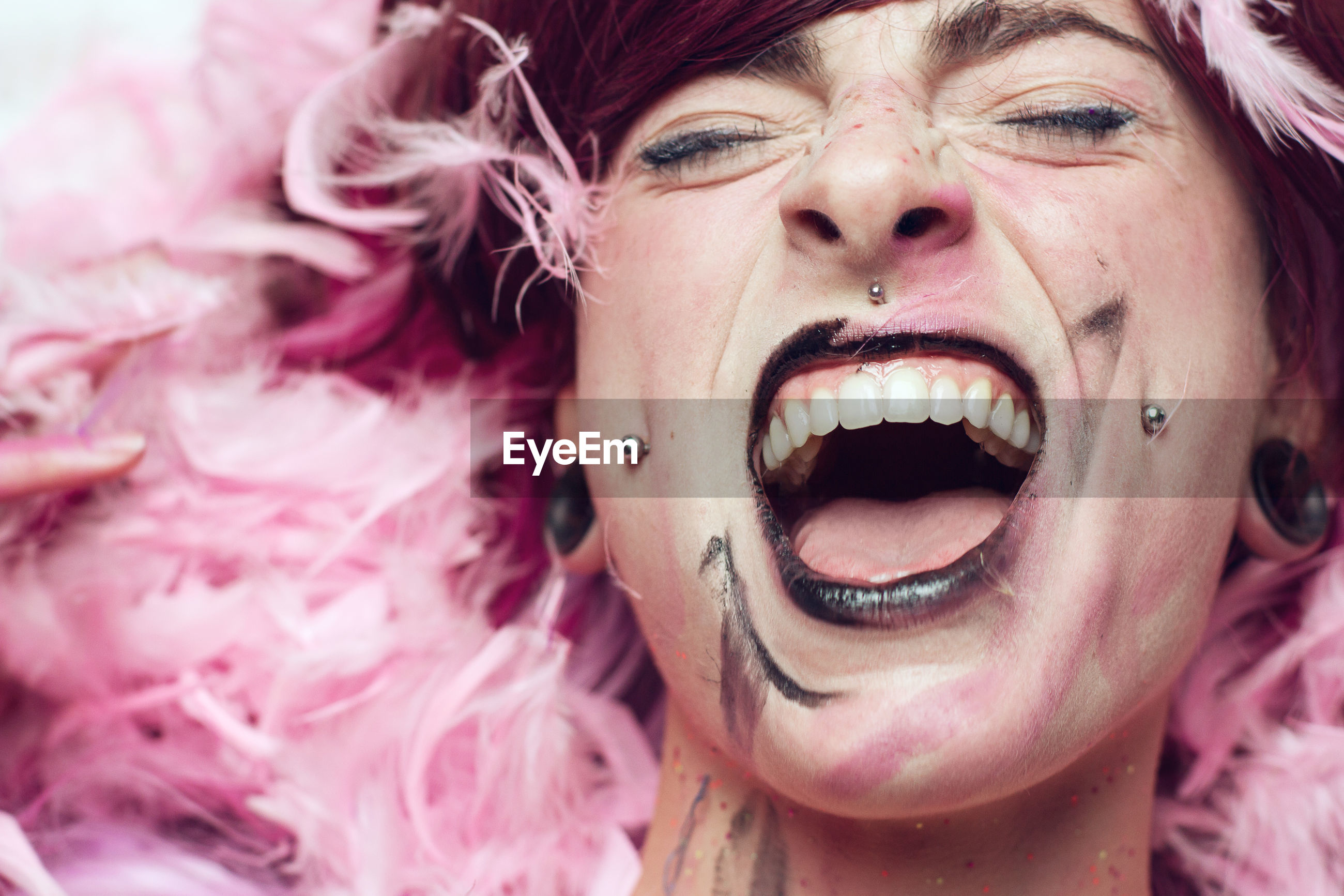 Close-up of woman with make-up screaming amidst pink feathers