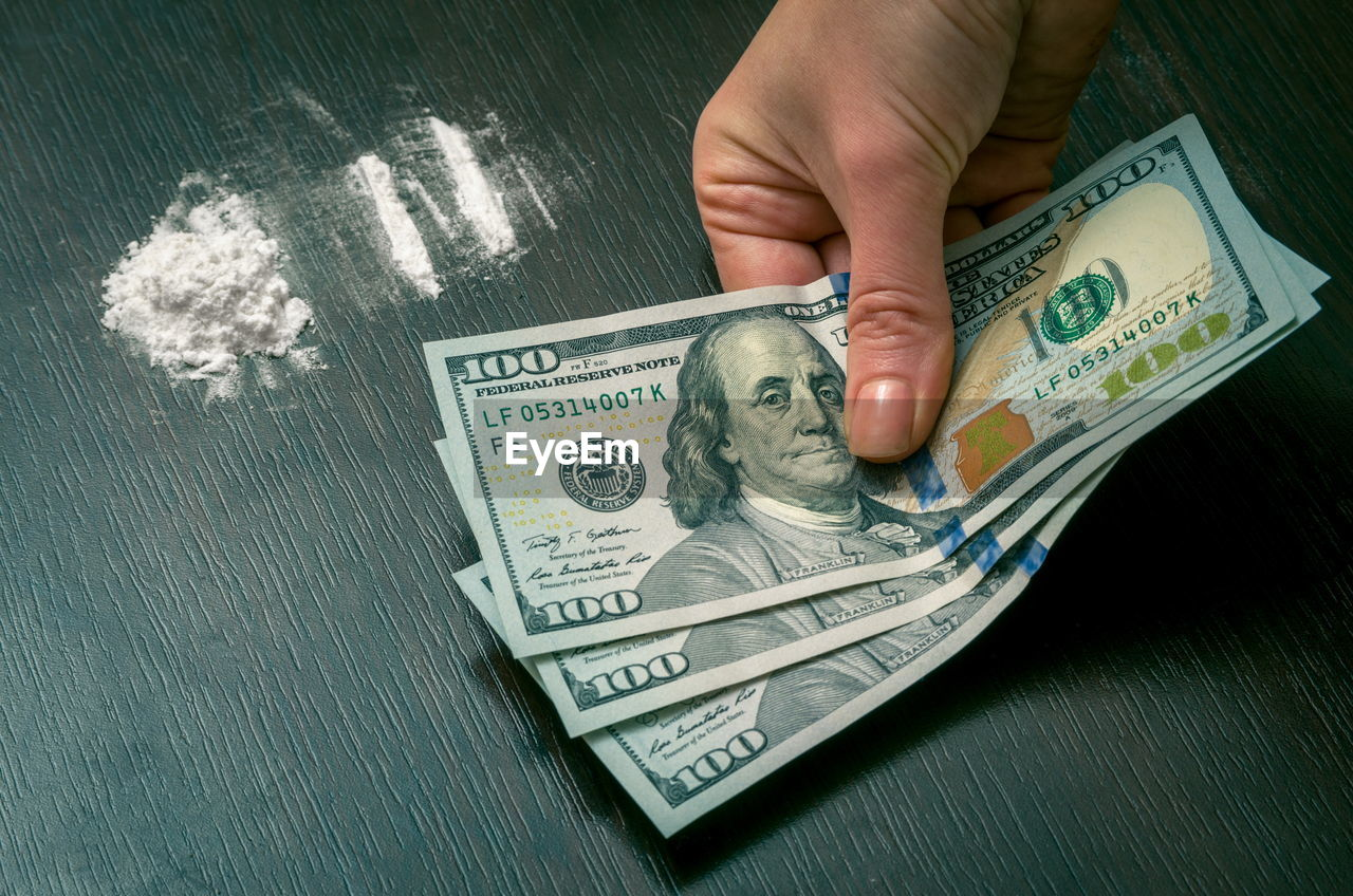 Cropped Hand Of Mid Adult Woman Holding Money By Cocaine On Table