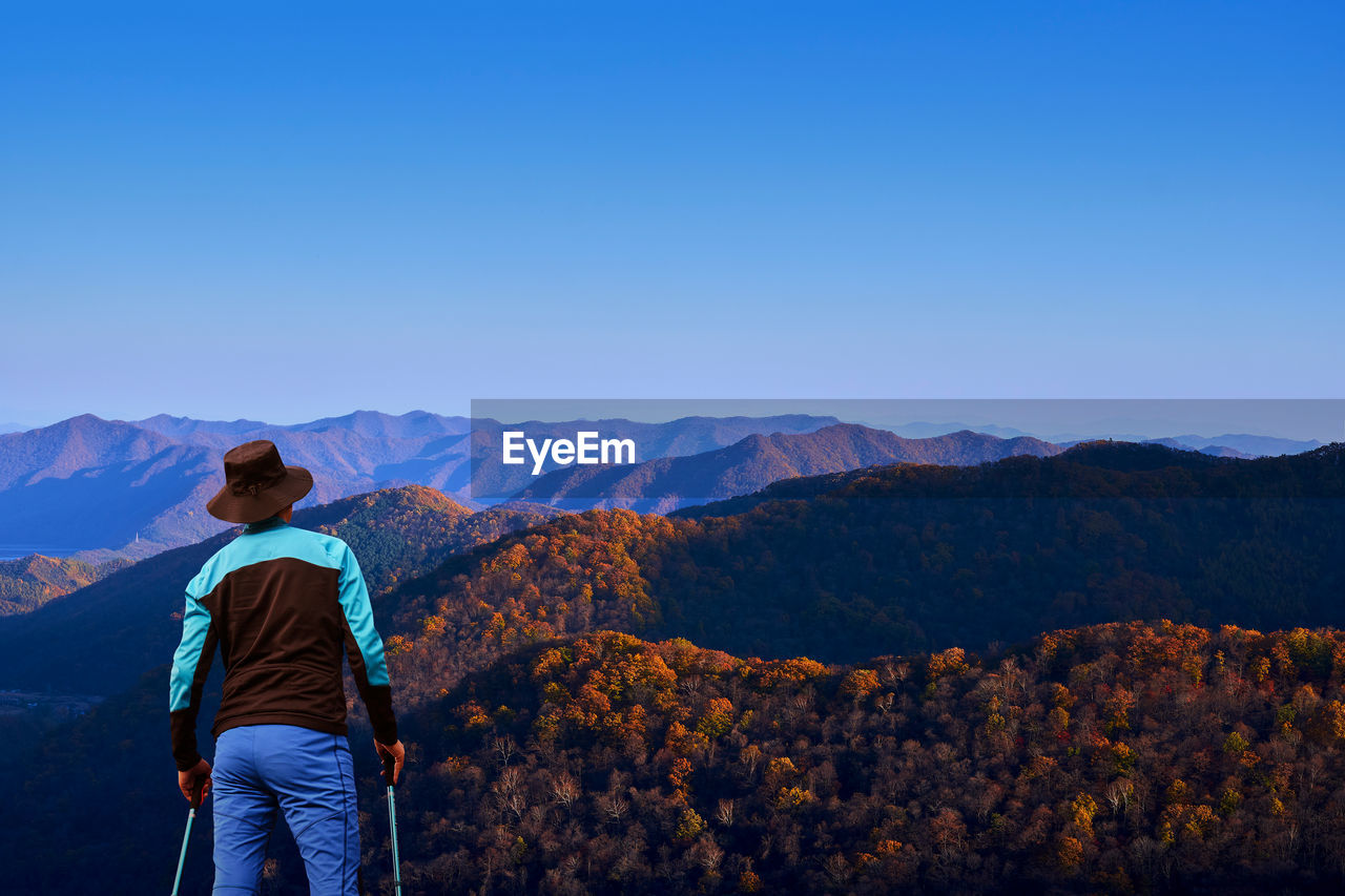 Rear View Of Man Looking At Mountains Against Clear Blue Sky