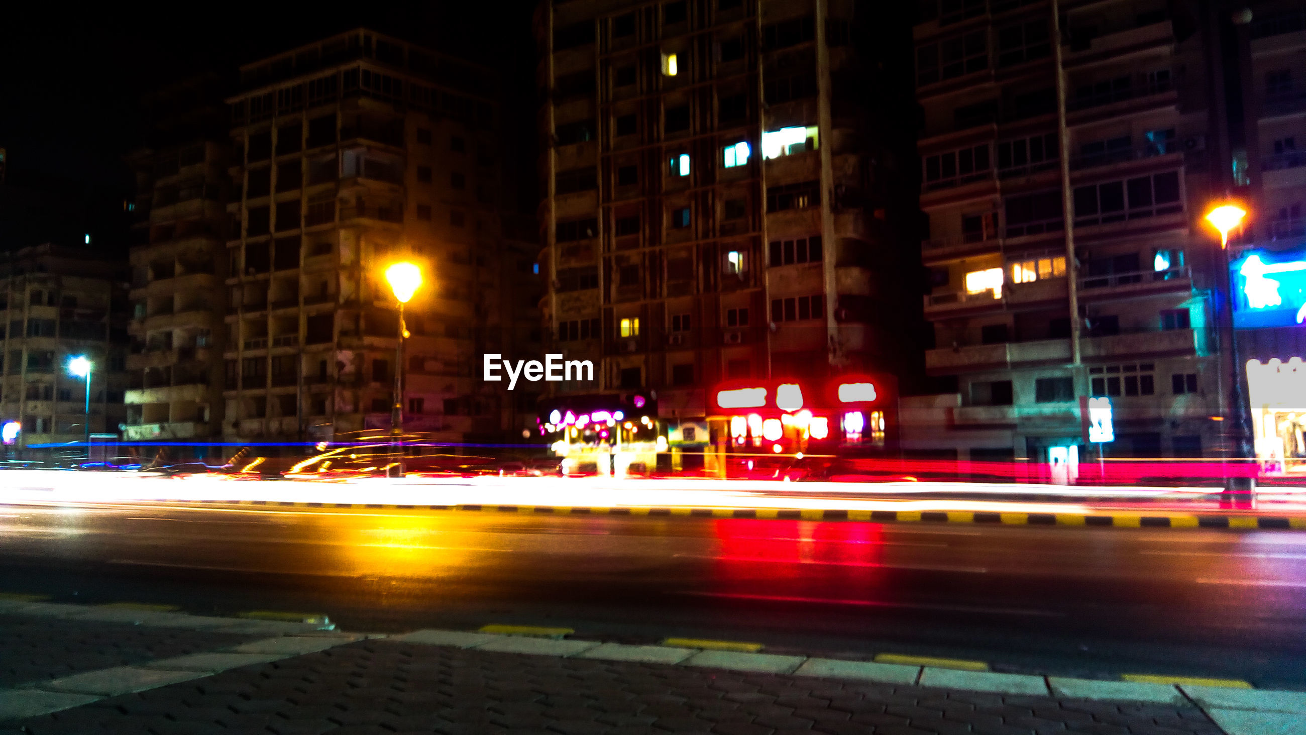 illuminated, night, building exterior, transportation, city, architecture, speed, street, motion, road, built structure, light trail, street light, long exposure, car, city life, high street, outdoors, no people