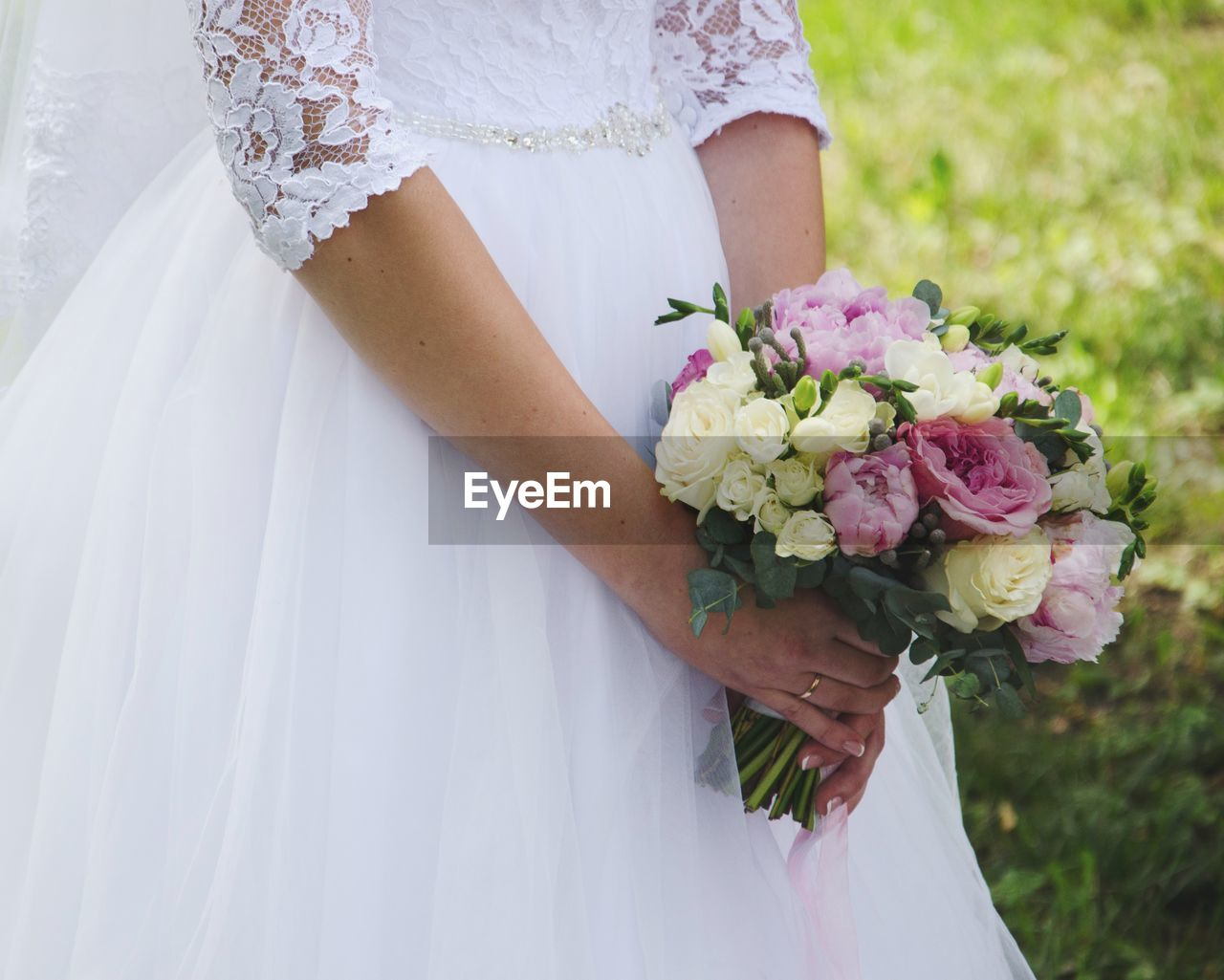 Midsection of bride holding bouquet against while standing in park