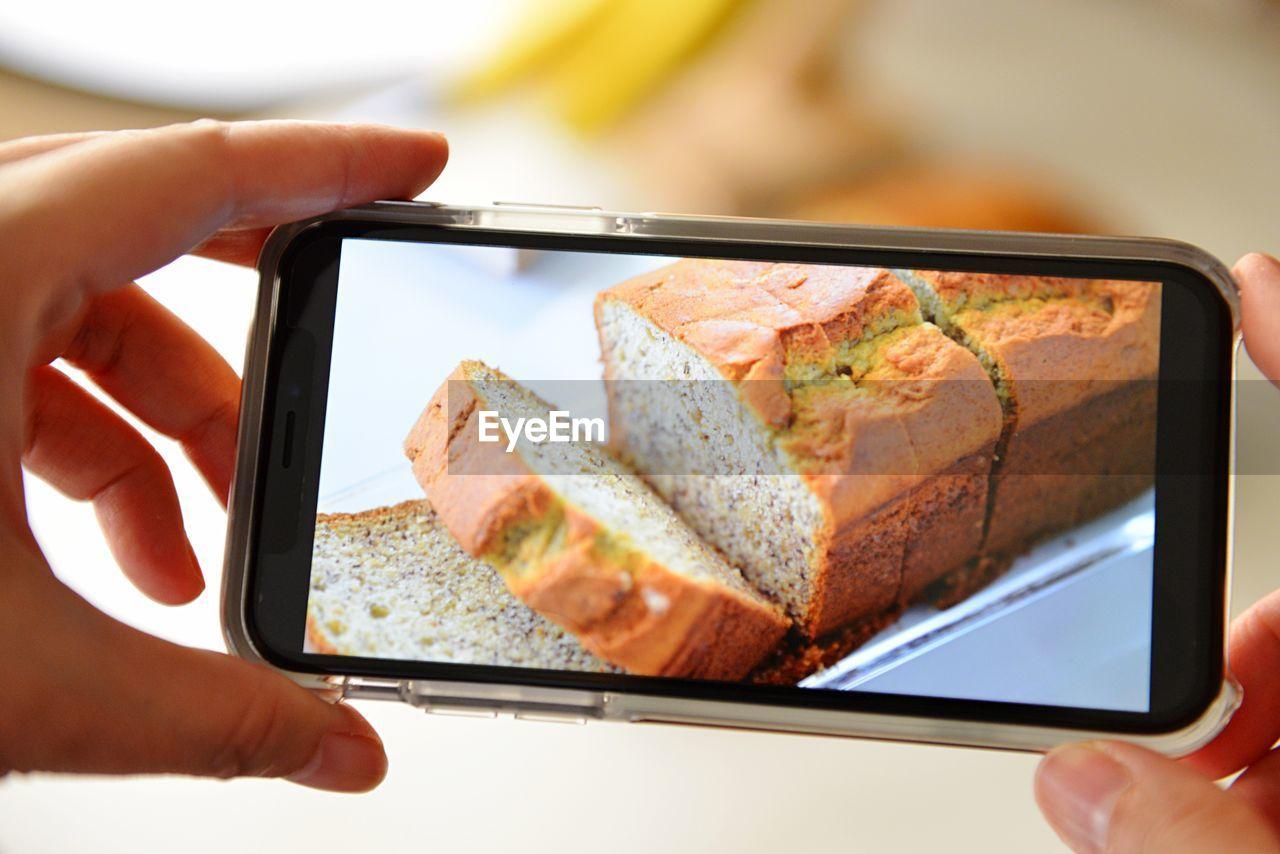 Close-Up Of Hand Photographing Bread On Smart Phone