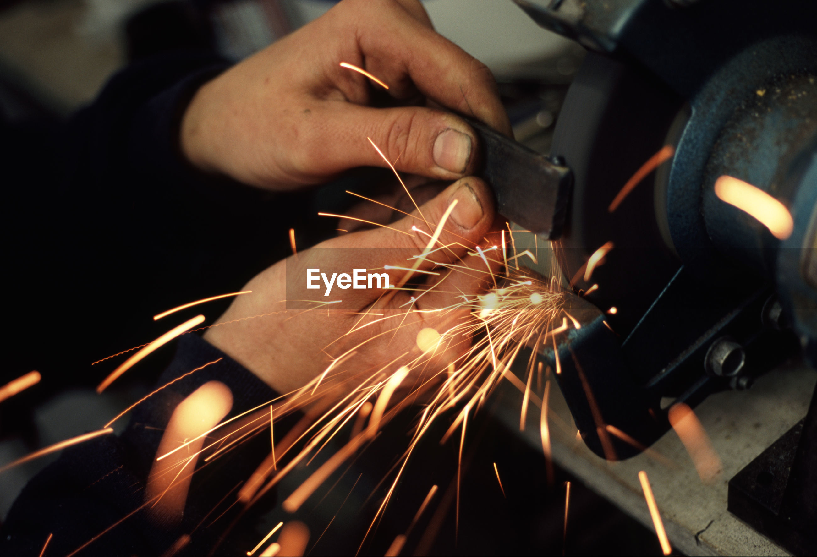 Sparks emitting while worker grinding iron