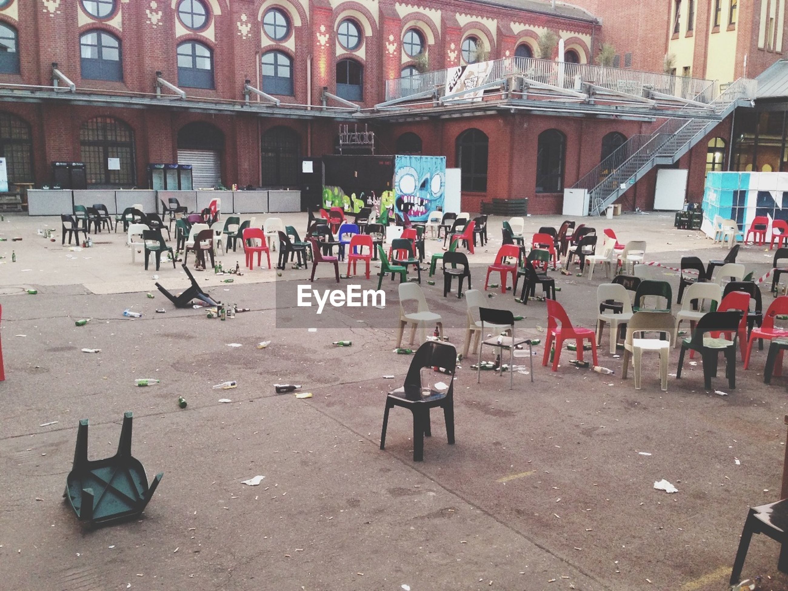 Messy town square with chairs and bottles
