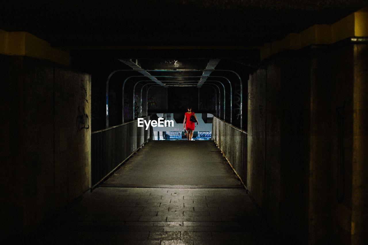 Rear View Of Woman Walking In Illuminated Underground Walkway