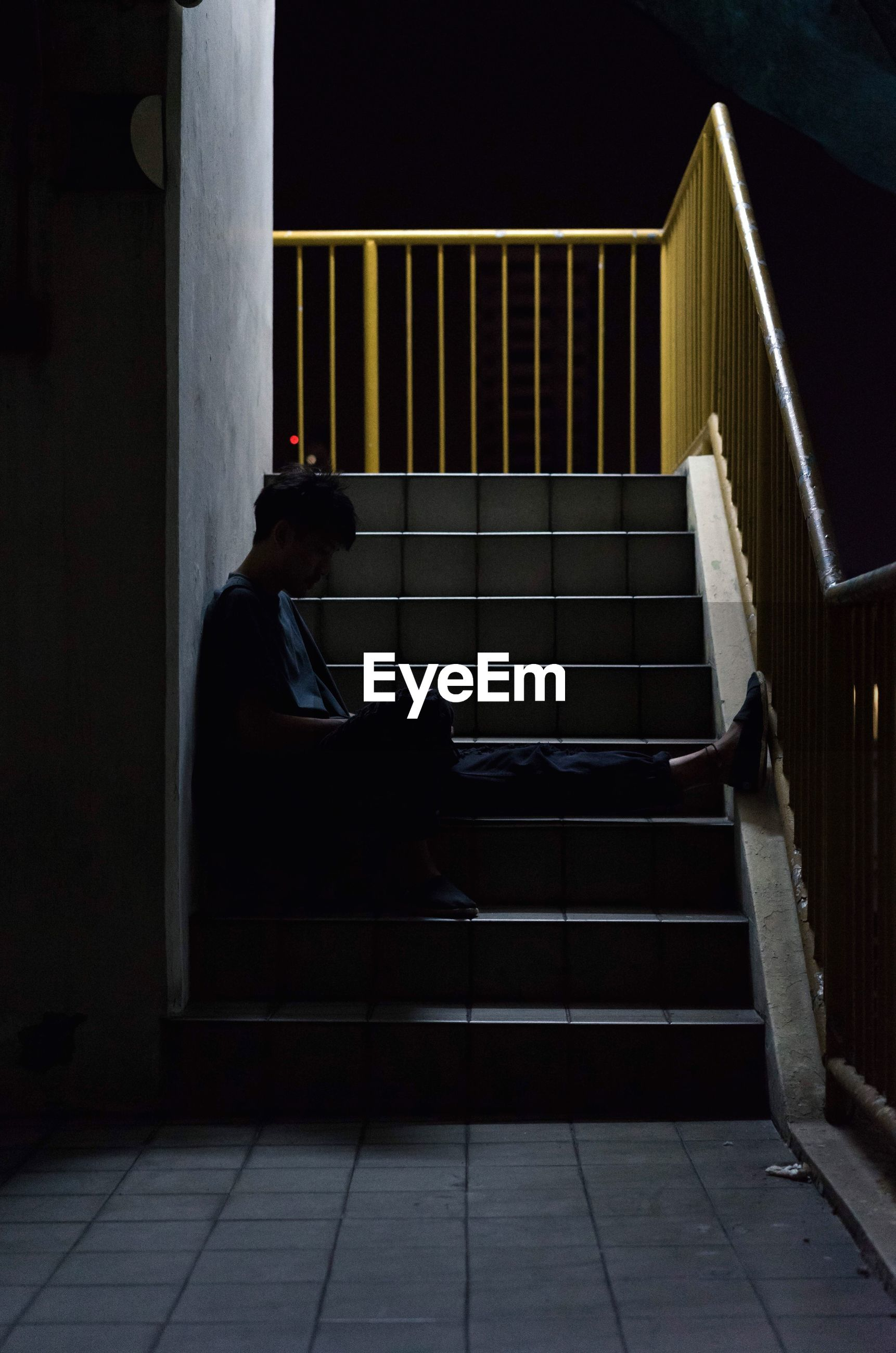 Full length side view of depressed man sitting on steps at night