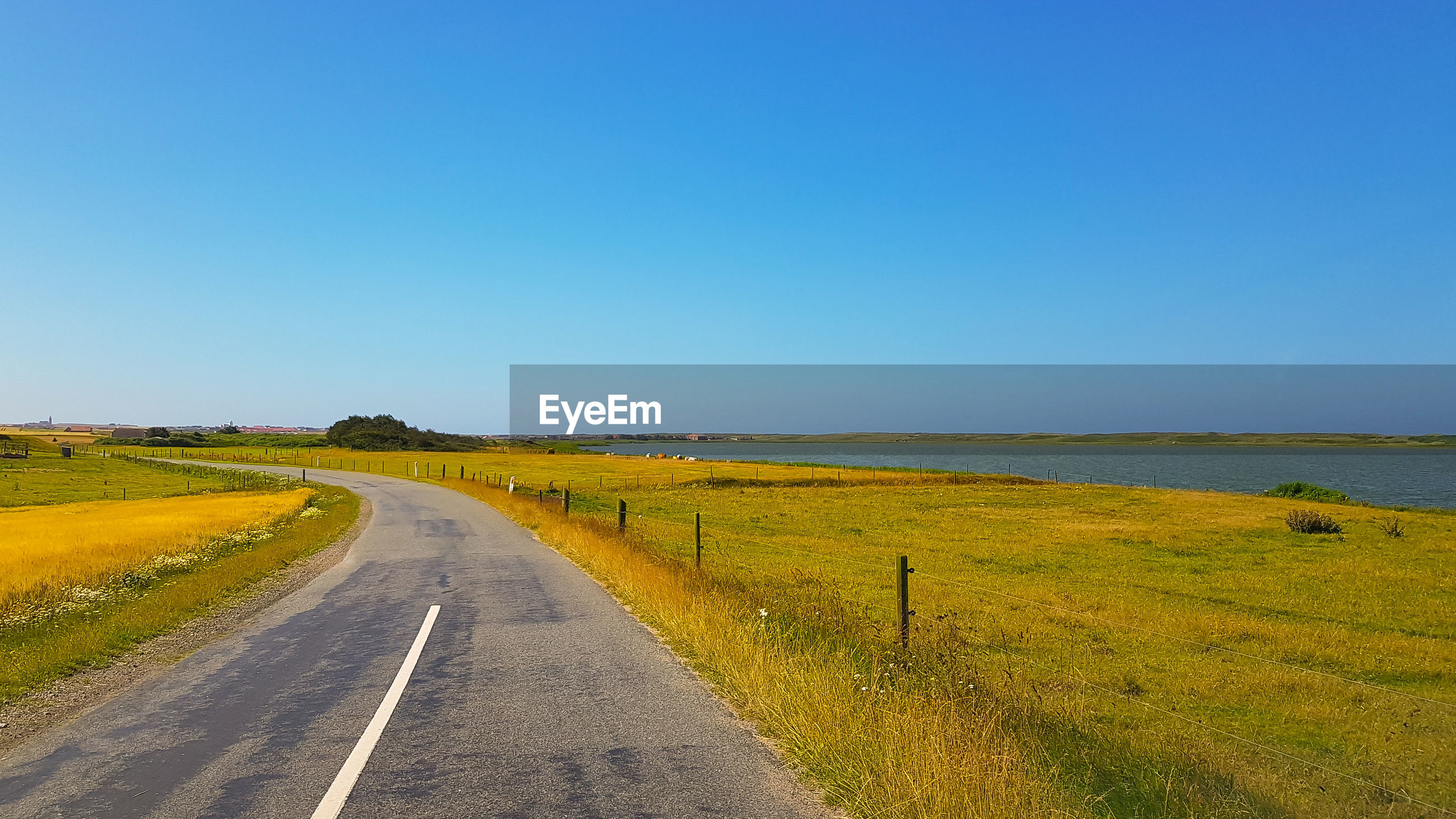 EMPTY ROAD ALONG COUNTRYSIDE LANDSCAPE AGAINST CLEAR BLUE SKY