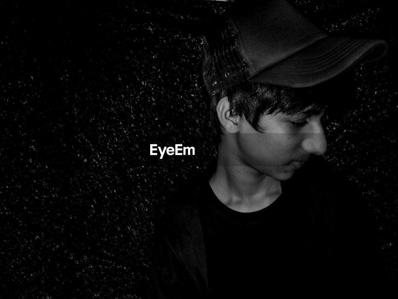 Teenage Boy Wearing Cap Looking Away While Standing Against Wall