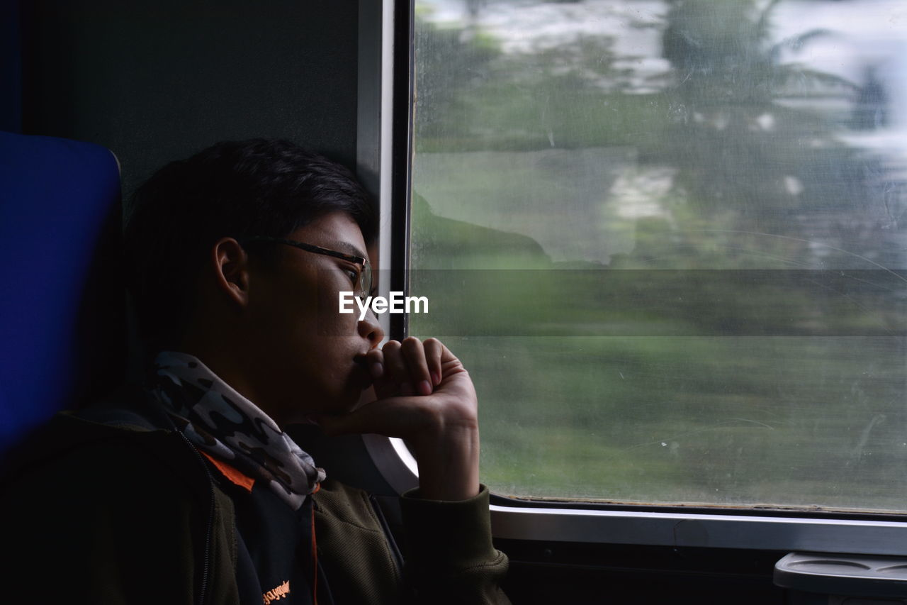 A man looking through train window