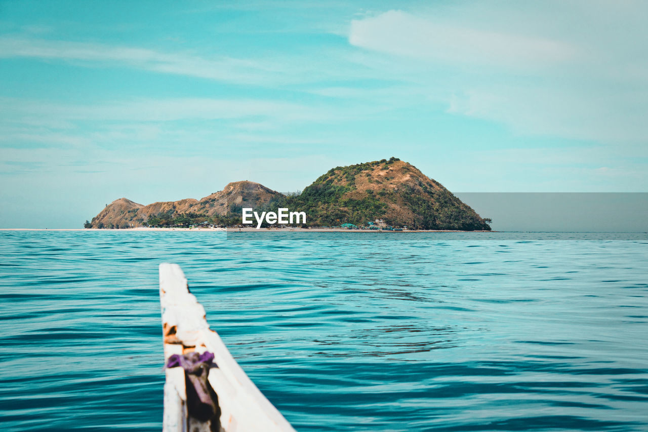 water, sea, sky, ocean, nature, beauty in nature, scenics - nature, horizon, land, vacation, nautical vessel, bay, tranquility, shore, vehicle, tranquil scene, transportation, travel, beach, day, coast, boat, cloud, travel destinations, holiday, outdoors, island, blue, islet, trip, boating, idyllic, rock, horizon over water, wave, mode of transportation, relaxation, no people, mountain