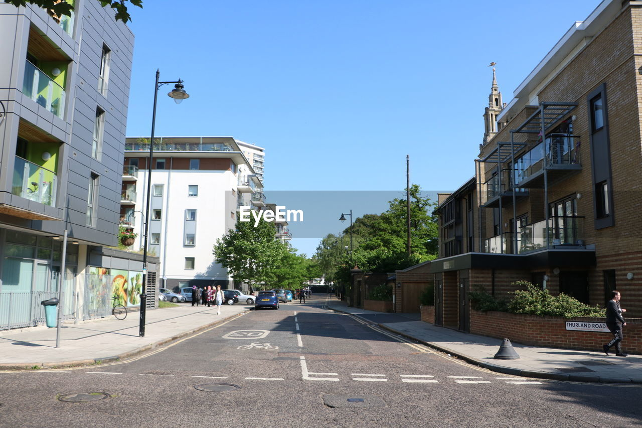building exterior, architecture, clear sky, built structure, street, outdoors, day, road, city, no people, tree, sky