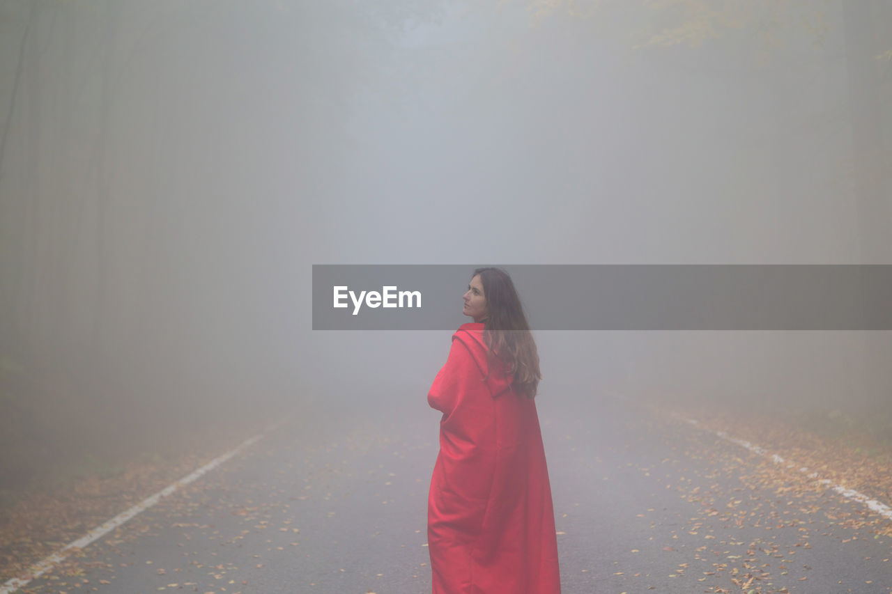 Woman Standing On Road In Foggy Weather