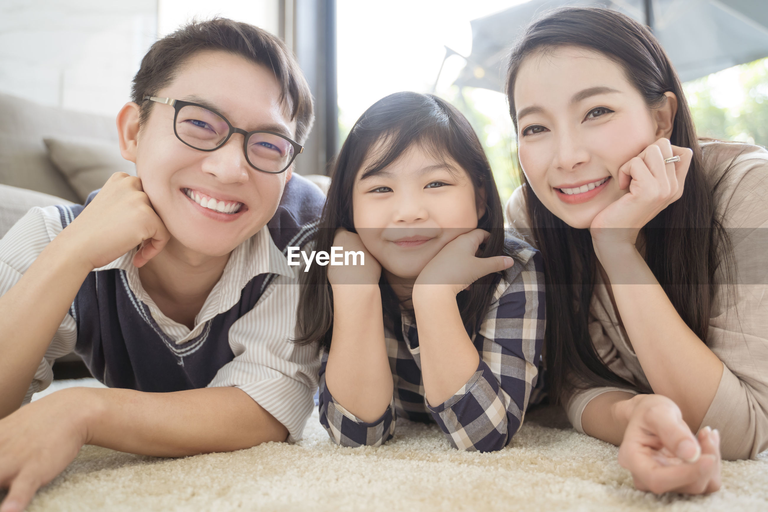Portrait of smiling parents lying down with daughter on rug in living room at home