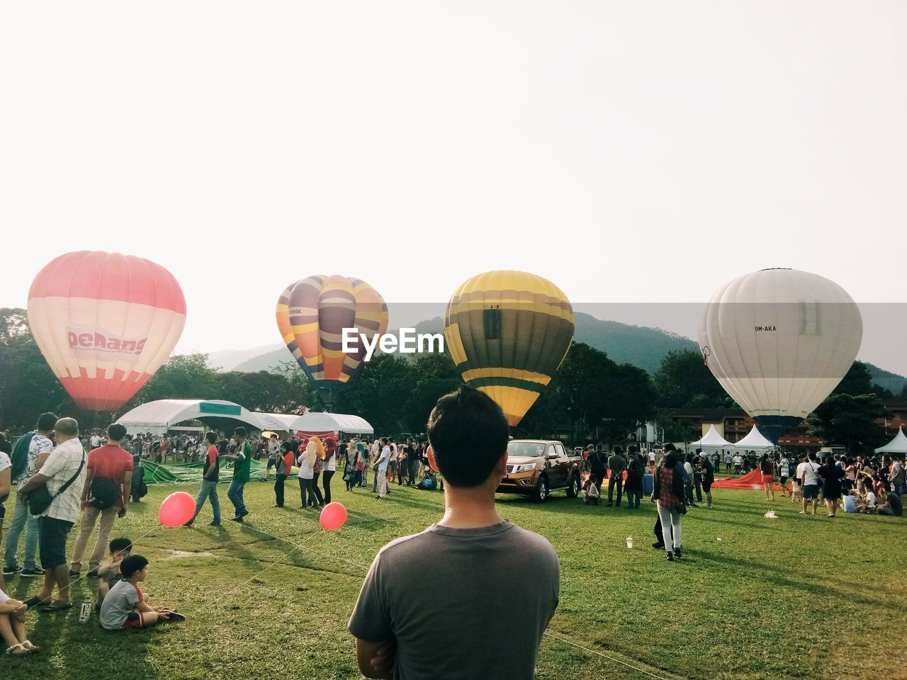 large group of people, real people, balloon, men, hot air balloon, women, grass, leisure activity, clear sky, ballooning festival, enjoyment, field, day, outdoors, building exterior, nature, sky, adult, people