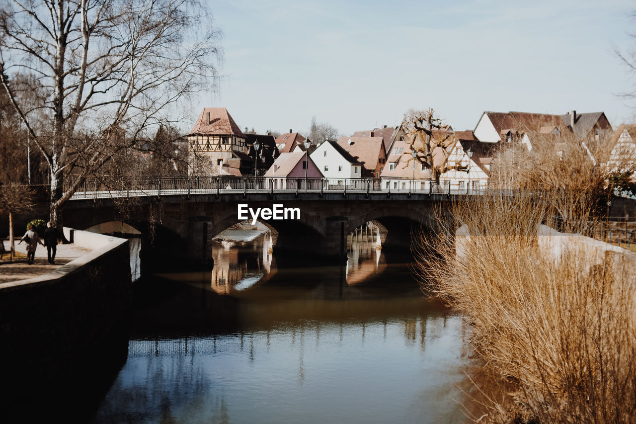 built structure, architecture, building exterior, water, sky, bare tree, bridge, connection, tree, bridge - man made structure, river, building, nature, day, waterfront, plant, no people, house, reflection, outdoors, arch bridge