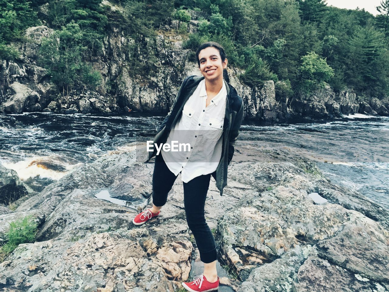 Portrait of smiling young woman standing on rock formation against river