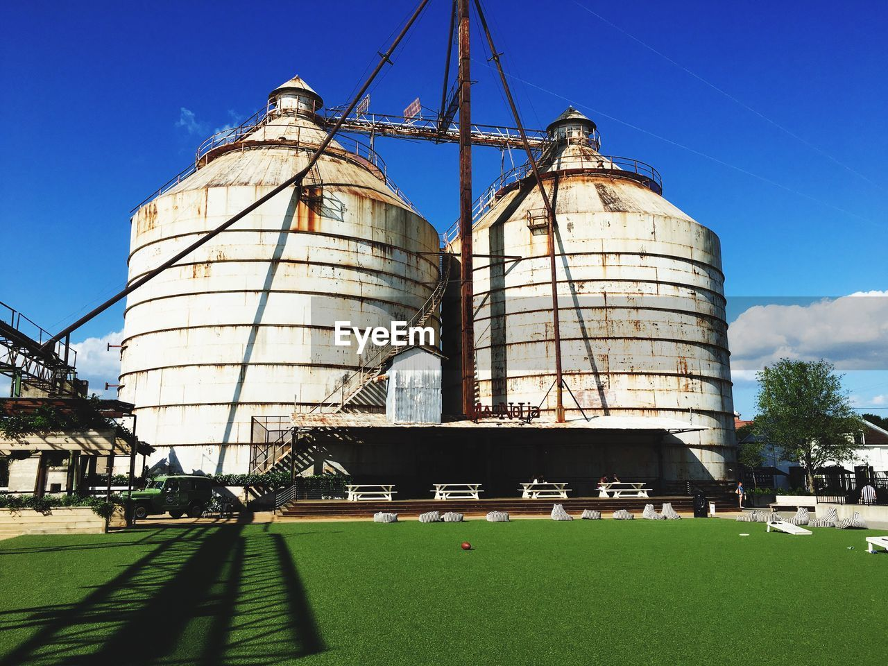 built structure, sky, architecture, building exterior, day, nature, storage tank, industry, factory, sunlight, outdoors, low angle view, plant, grass, cloud - sky, silo, metal, fuel and power generation, no people, fuel storage tank, water conservation