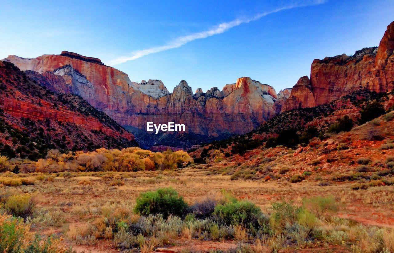Scenic View Of Landscape And Rocky Mountains Against Sky