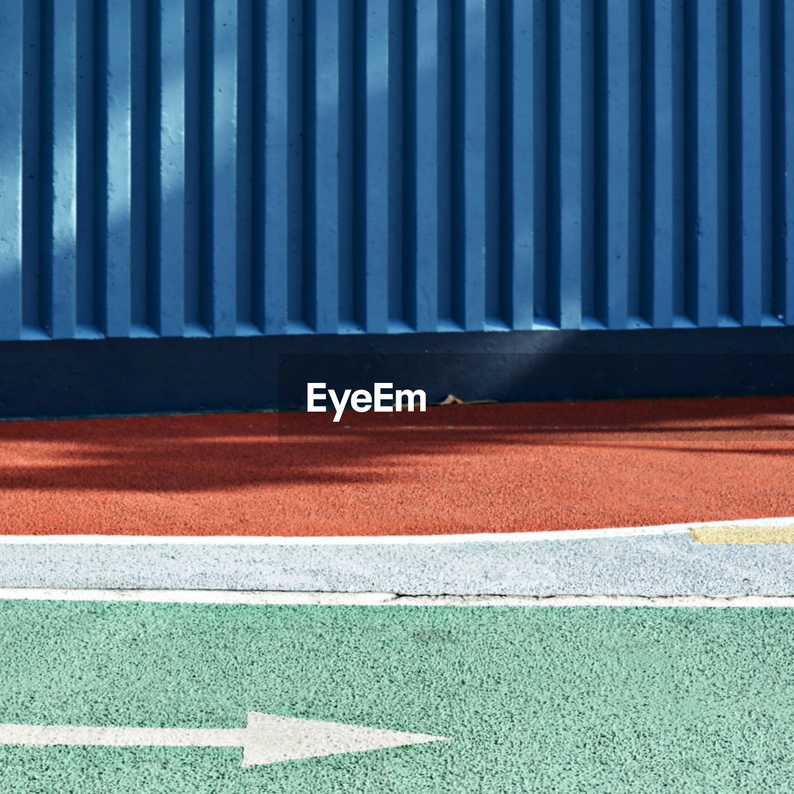 Directional sign on sports track by wall