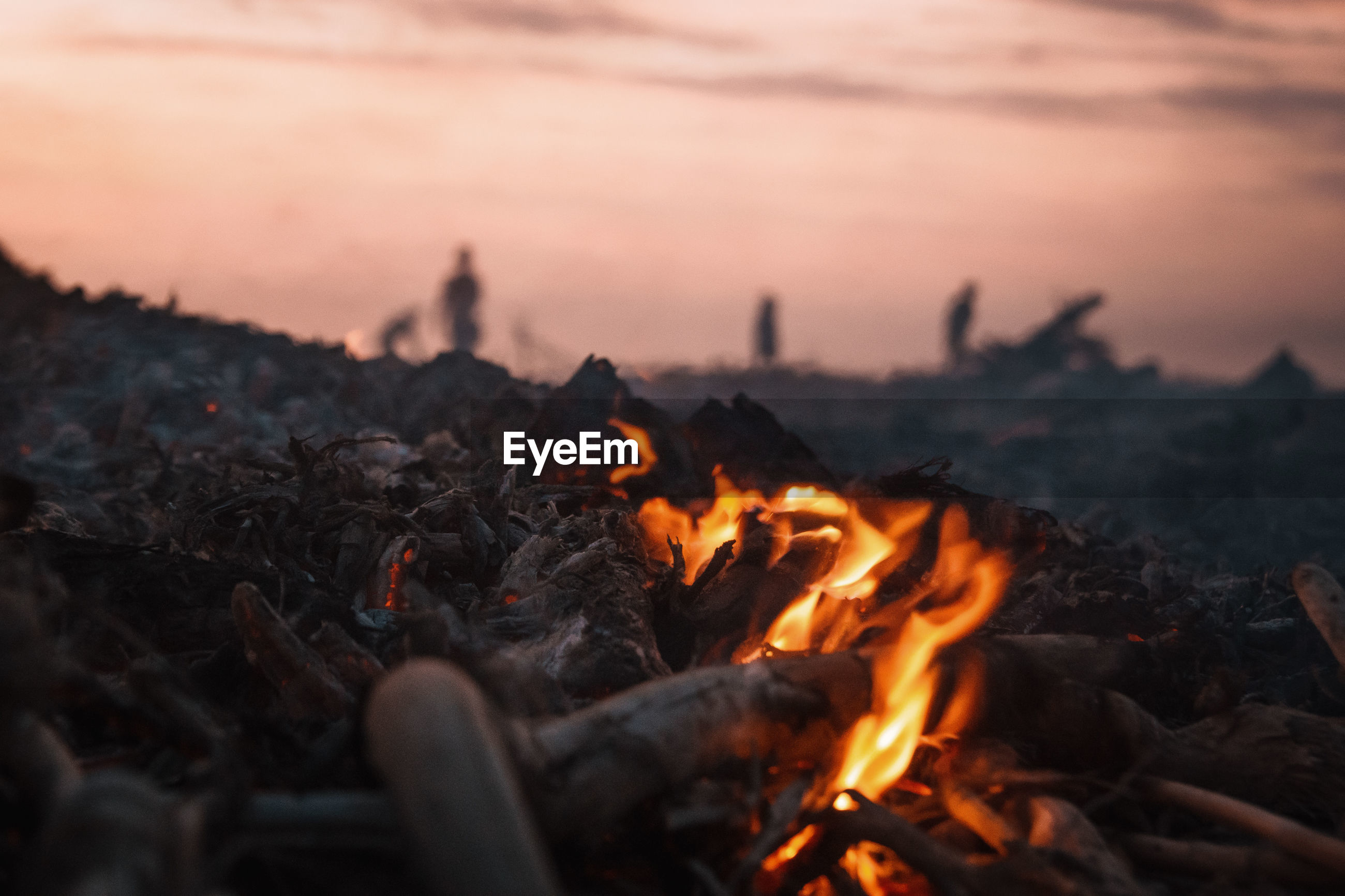Close-up of bonfire against sky during sunset