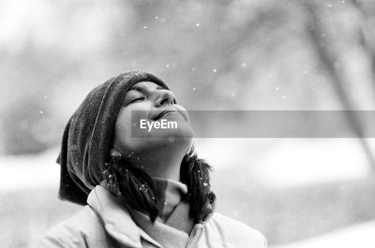 Close-Up Of Smiling Young Woman Enjoying Snowfall