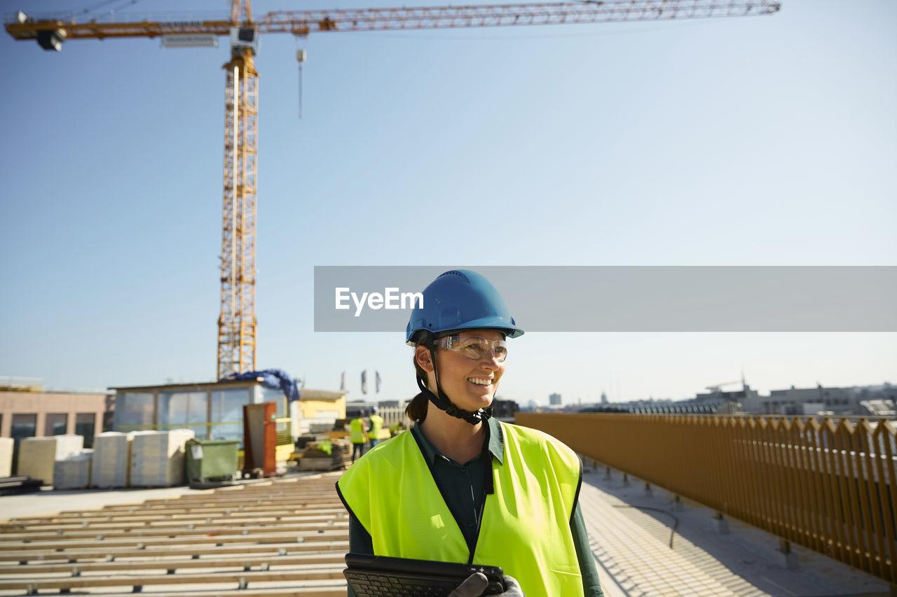 PORTRAIT OF SMILING MAN AT CONSTRUCTION SITE