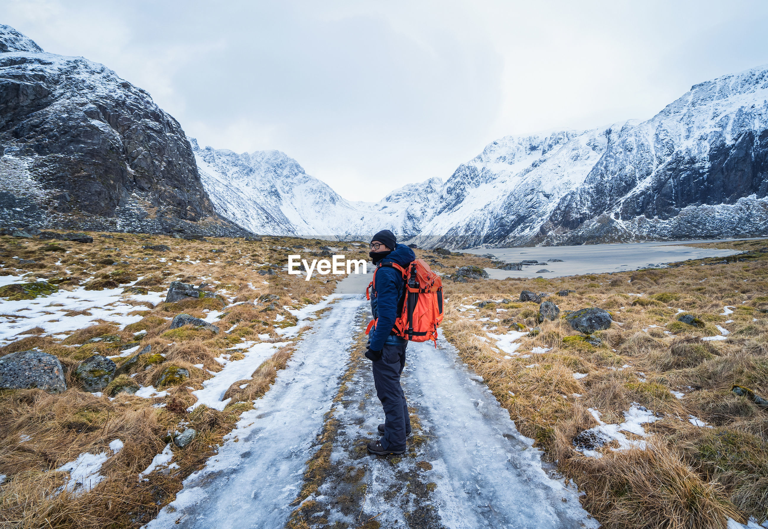 REAR VIEW OF MAN WALKING ON SNOWCAPPED MOUNTAINS AGAINST SKY
