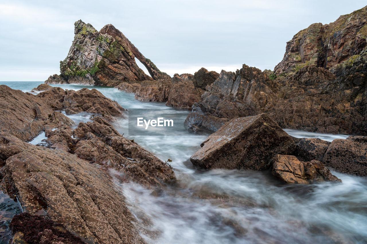 Scenic View Of Rocks In River Against Sky