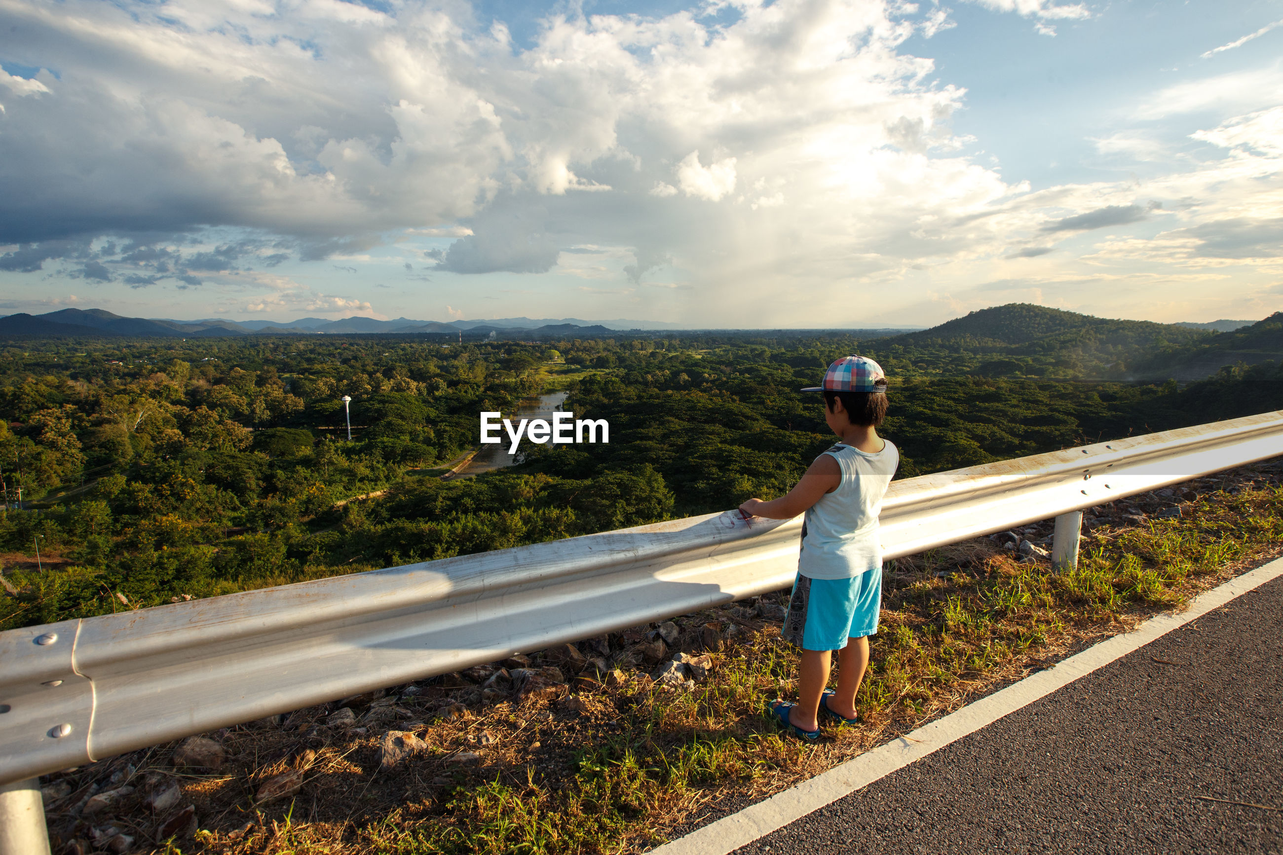Rear view of boy looking at landscape by railing