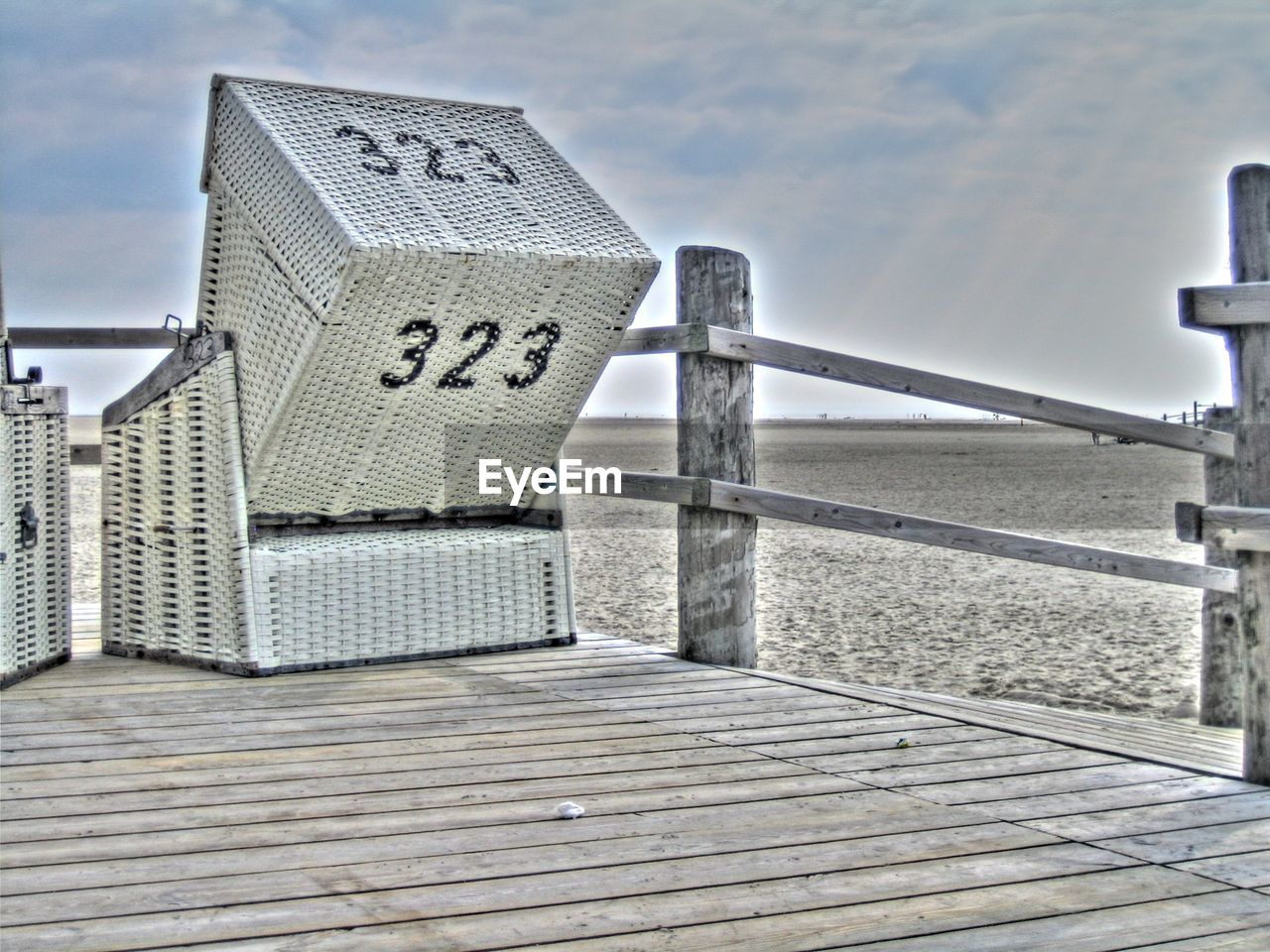 sky, water, day, nature, sea, railing, architecture, no people, cloud - sky, built structure, wood - material, hooded beach chair, outdoors, communication, focus on foreground, footpath, pier, text, beach