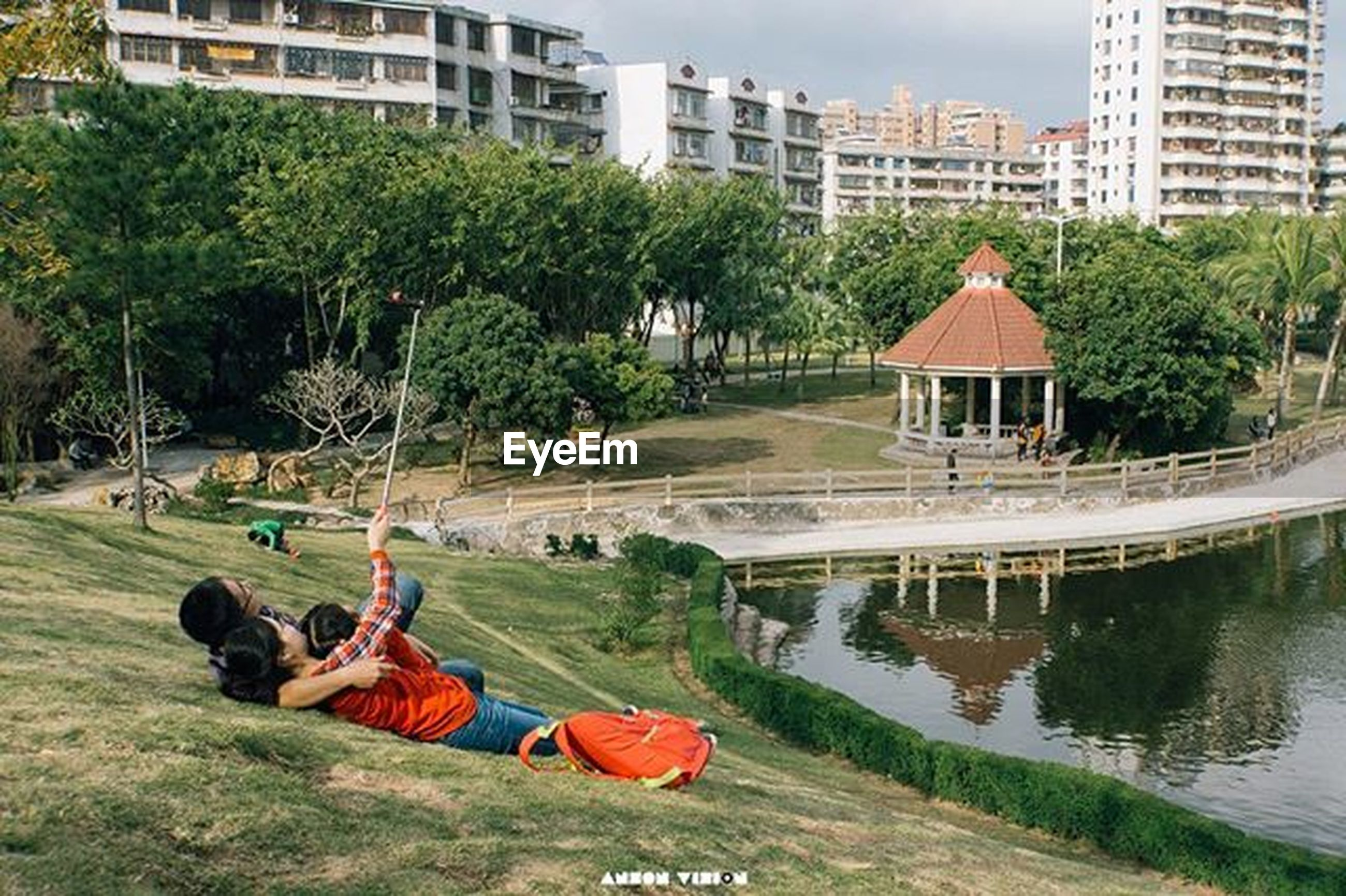 building exterior, architecture, built structure, water, tree, grass, city, pond, fountain, waterfront, river, reflection, green color, park - man made space, swimming pool, leisure activity, lifestyles, outdoors, incidental people