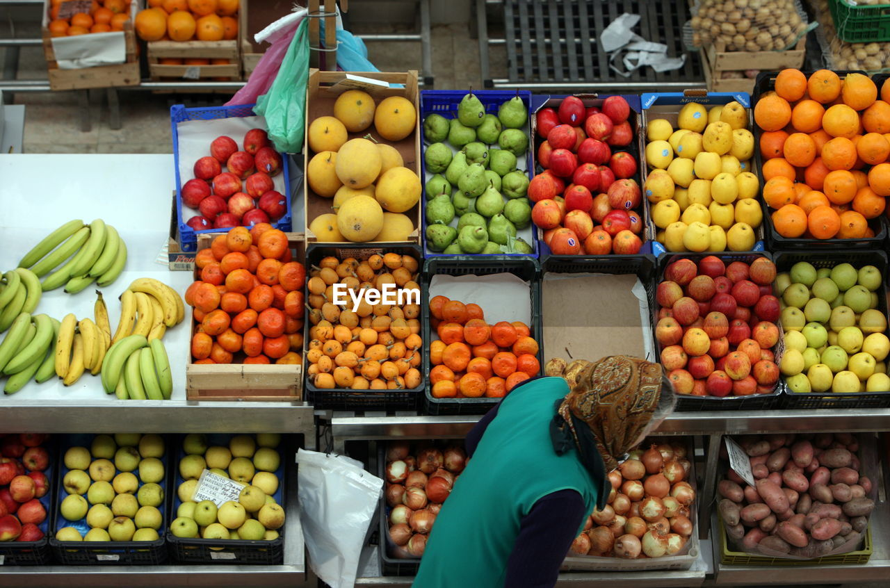 Woman against fruits in crates at market stall