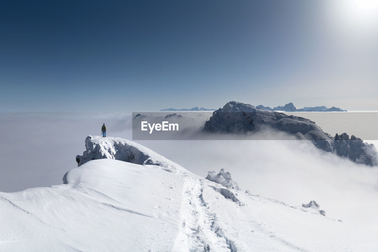 Person Standing On Snowcapped Mountain Against Sky