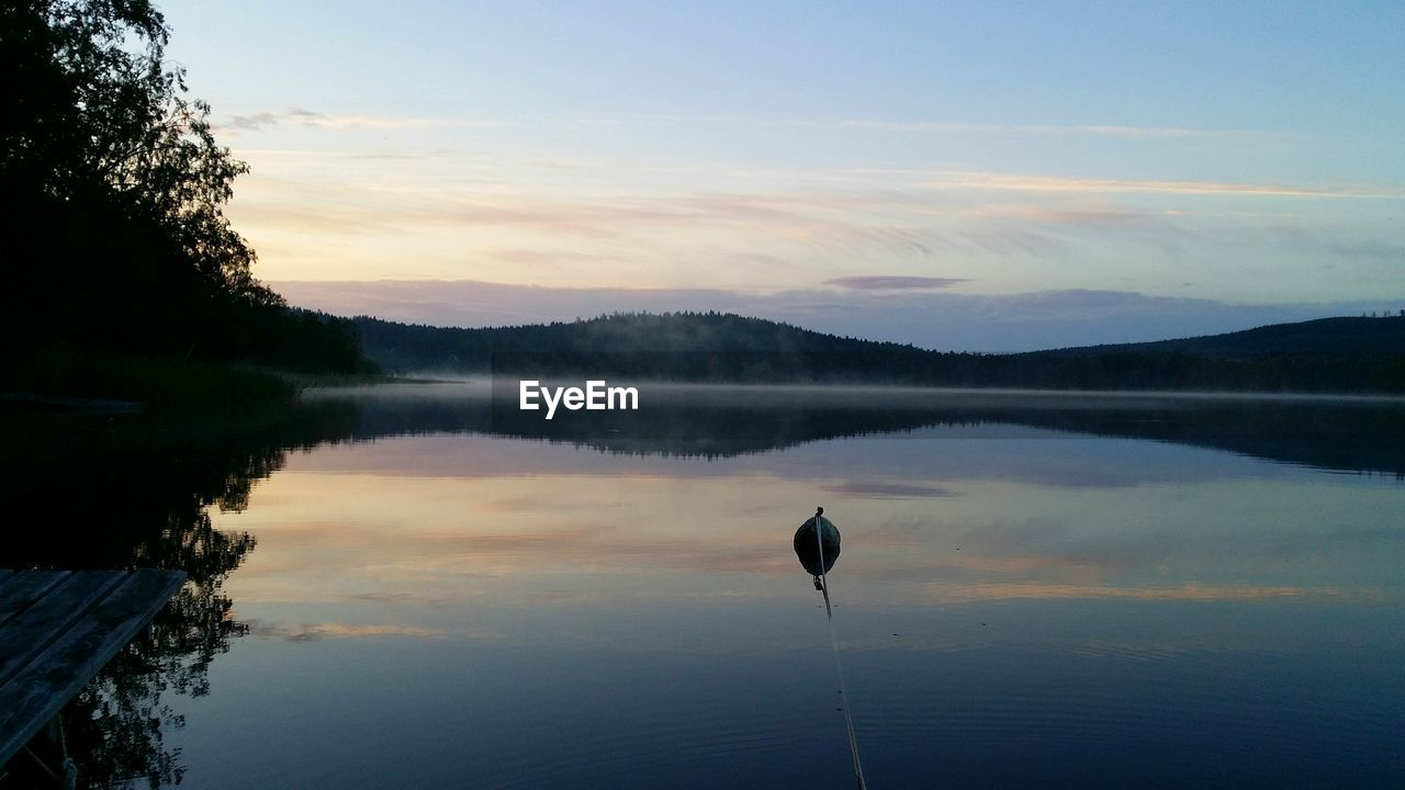 Scenic View Of Calm Lake Against Sky During Sunset