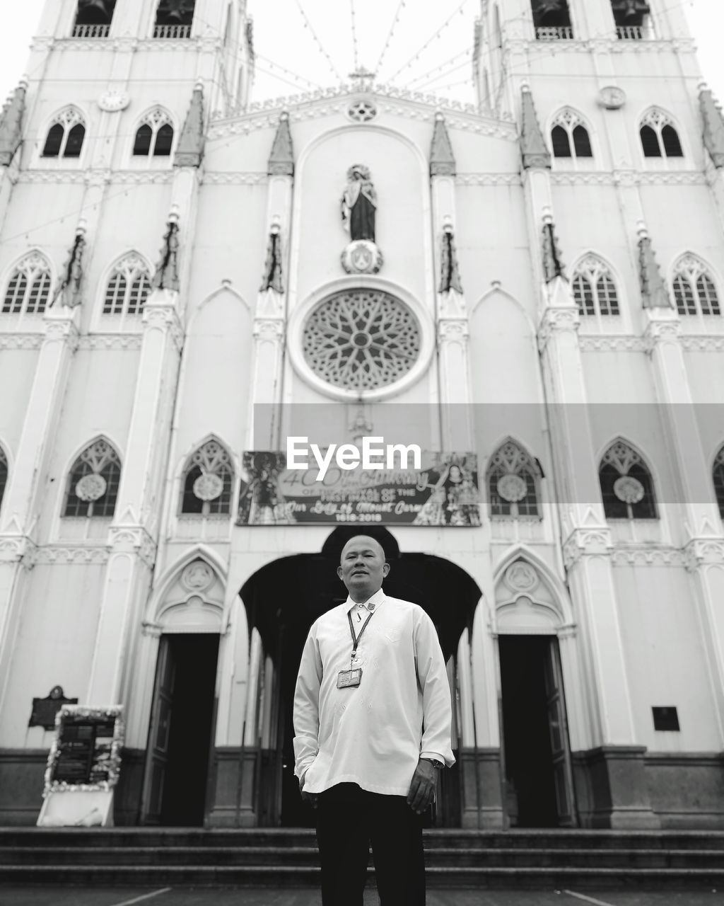 real people, religion, front view, place of worship, one person, spirituality, architecture, looking at camera, standing, built structure, young adult, portrait, lifestyles, low angle view, day, young men, leisure activity, building exterior, indoors