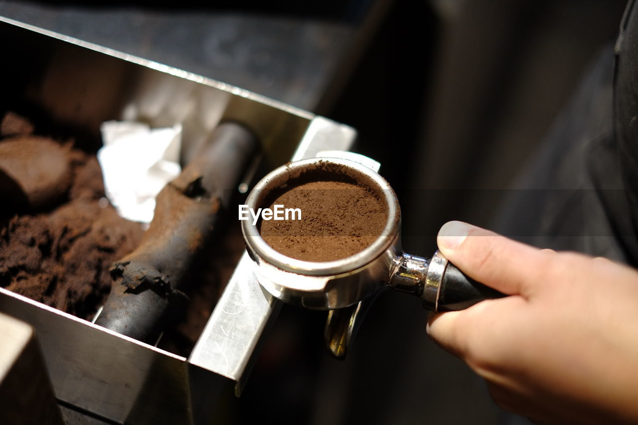human hand, coffee, coffee - drink, food and drink, hand, drink, cup, human body part, coffee cup, holding, mug, real people, refreshment, ground coffee, one person, indoors, freshness, close-up, focus on foreground, coffee maker, preparation, body part, frothy drink, finger, coffee shop, barista