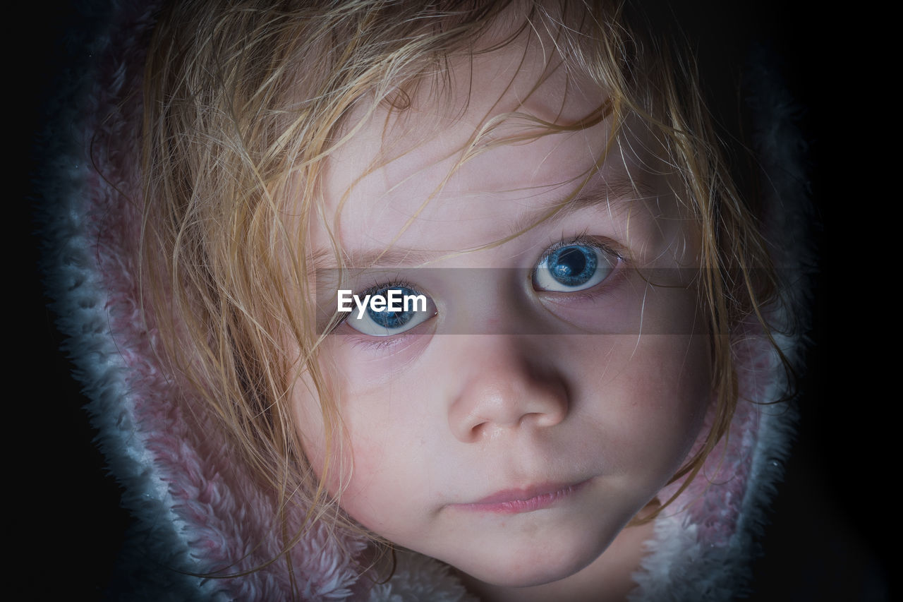 Close-up portrait of cute girl with blue eyes against black background