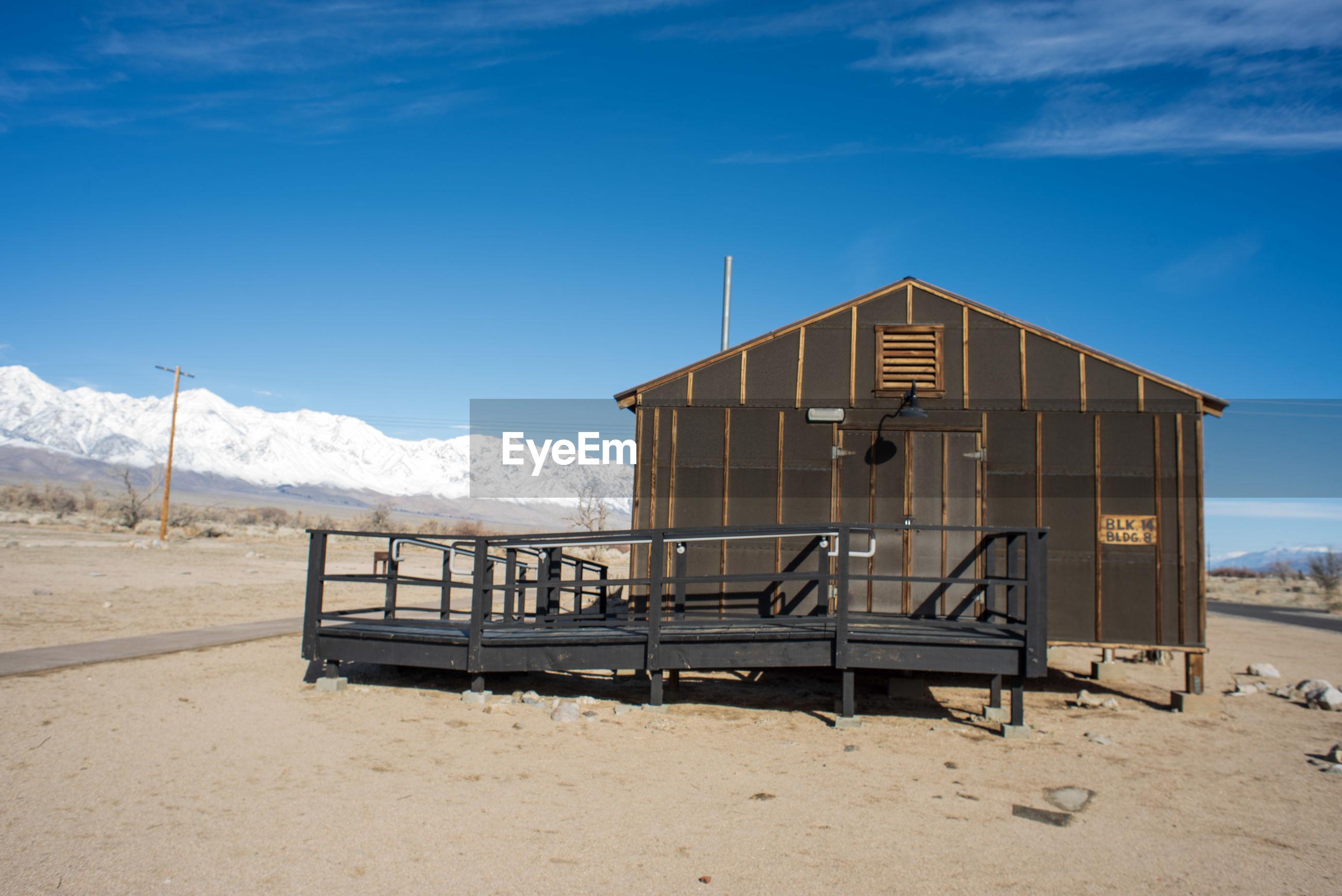 Concentration camp barracks on desert land against blue sky