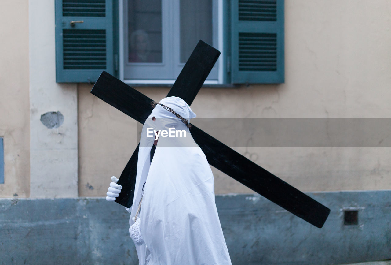 Man Walking With Cross Against Building