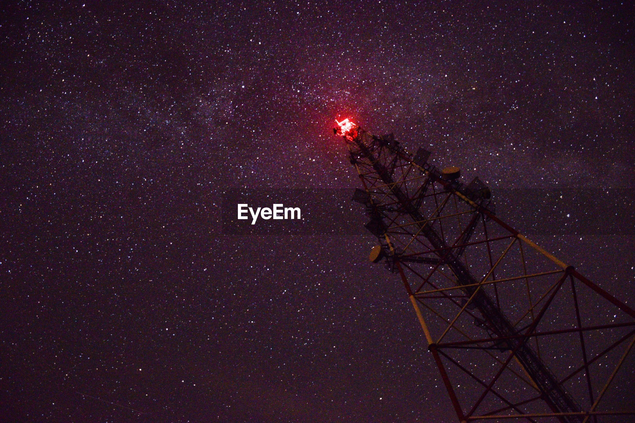 Low angle view of communications tower against sky at night