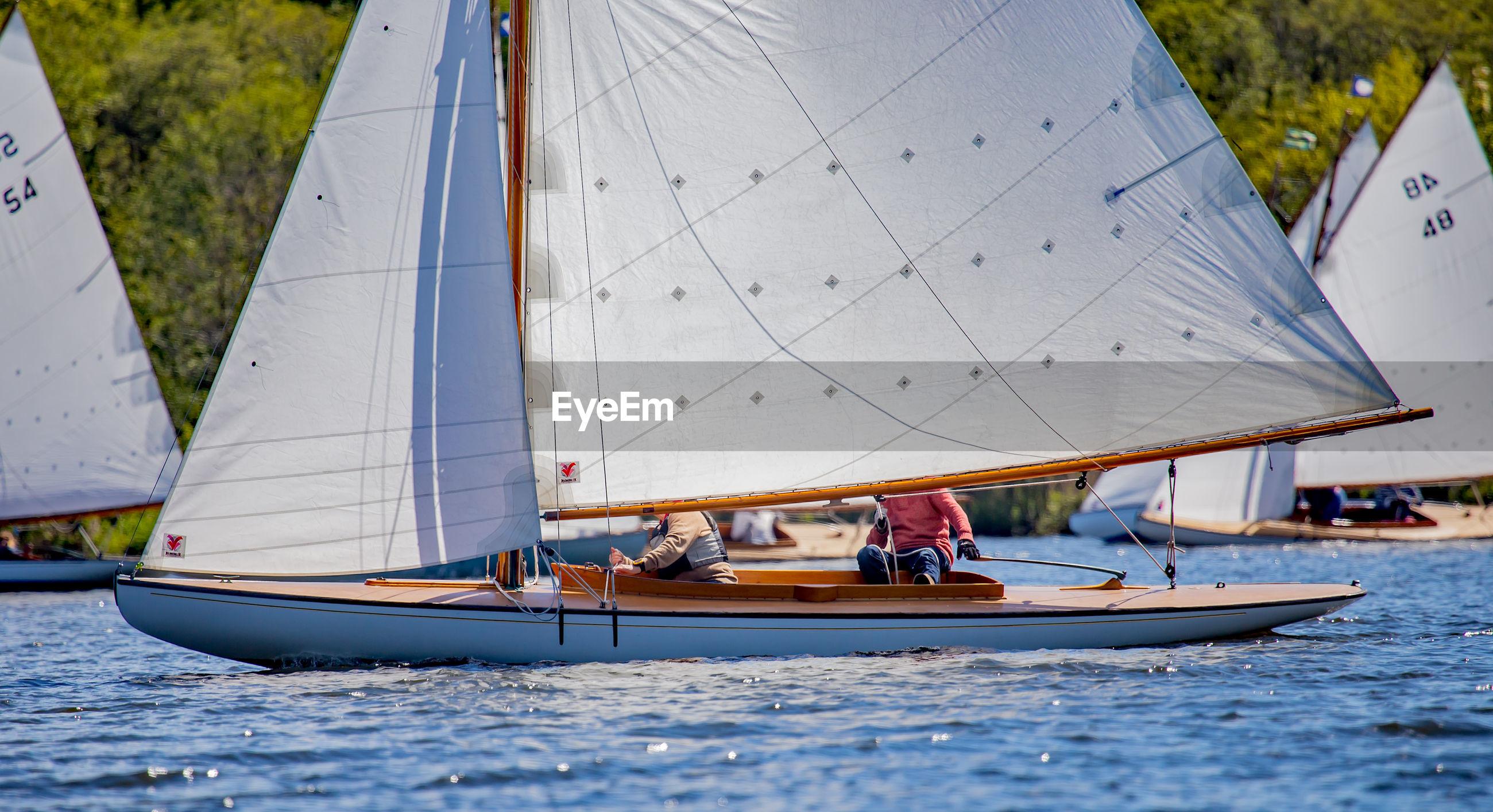 Men on sailboats sailing in sea