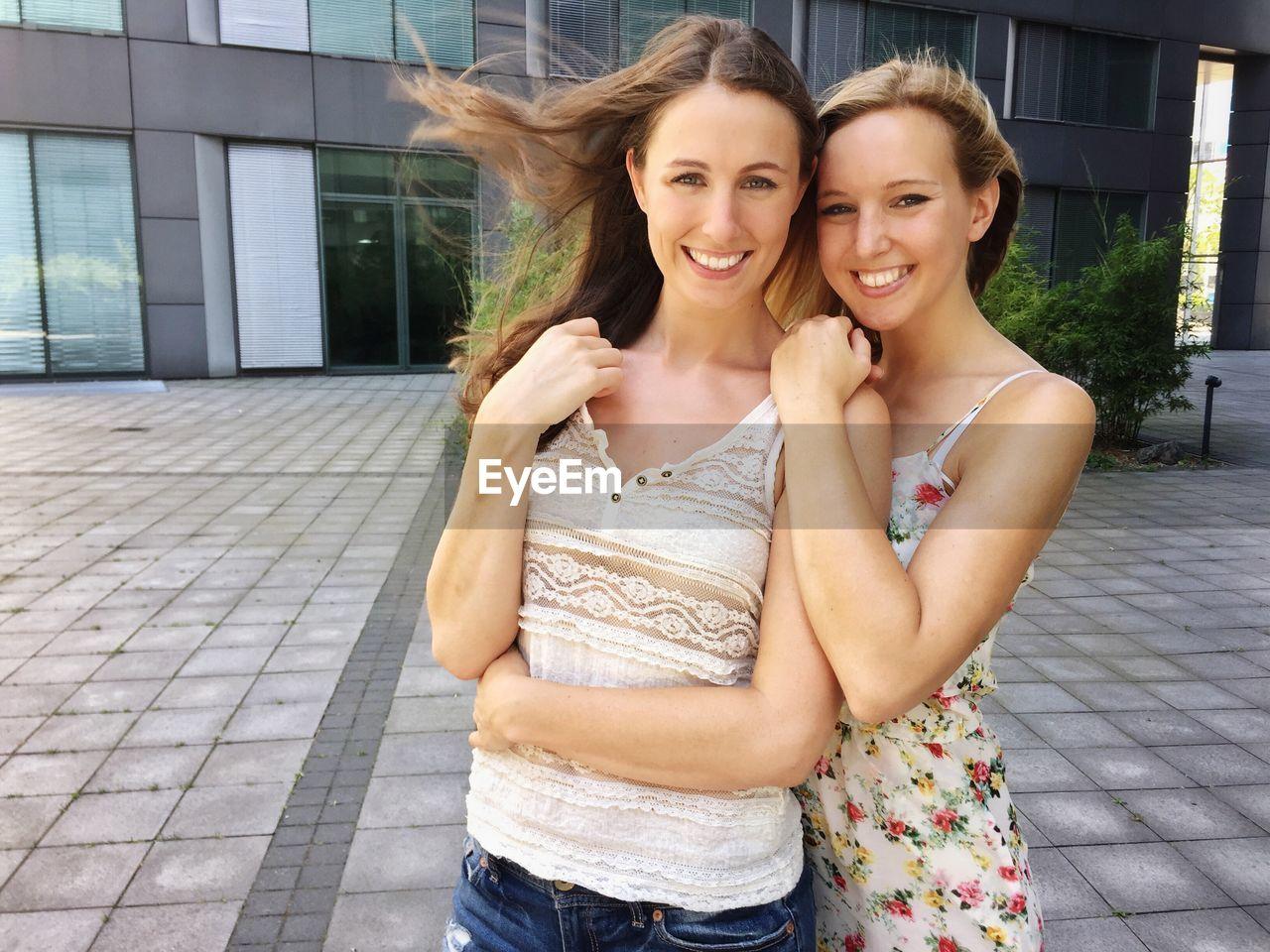 Portrait of happy friends embracing against building