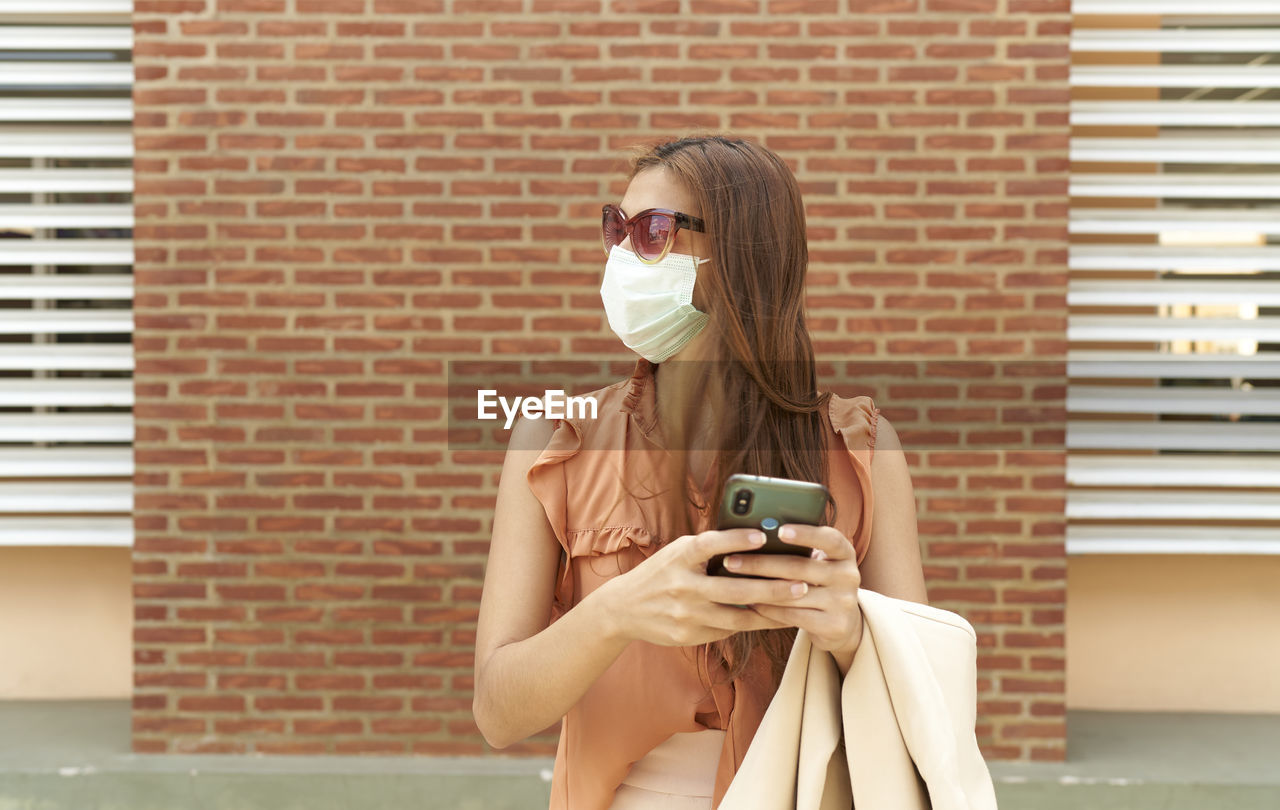 Woman standing on brick wall, young businesswoman with her mask talking with her cell phone